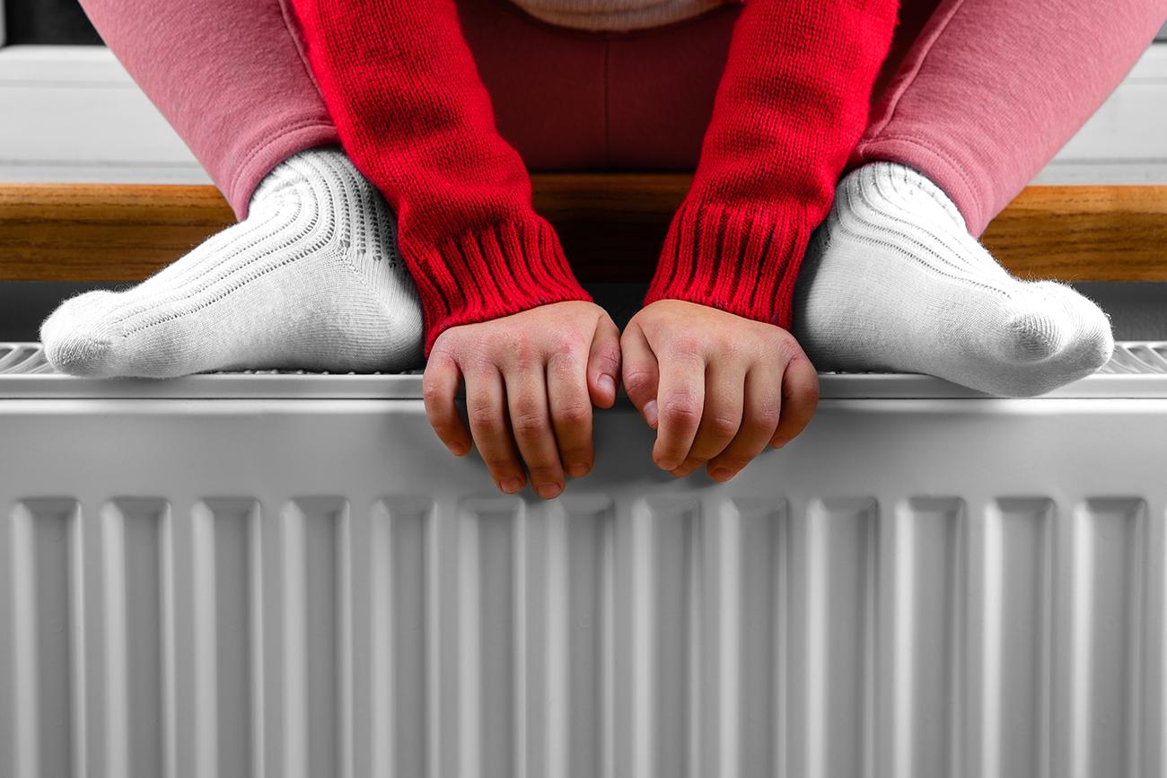 little girl warms her hands feet radiator